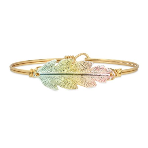 Lucky Feather Bangle Bracelet in Rainbow. Mood-lifting color takes this fan favorite bracelet to new heights of fashion. This limited-edition piece is uniquely finished by a state-of-the-art plating process for a gorgeous pastel rainbow effect. handcrafted in the USA by luca + danni