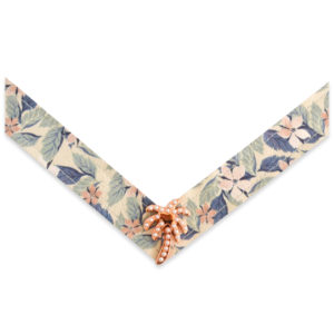 The Penelope Strap is a green, pink, and purple floral print on a cream base strap with a rose gold and pearl palm tree ornament.