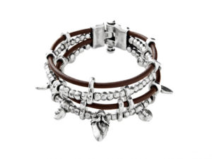 A wide bracelet with a leather strap base decorated with silver plated beads of different designs and pieces based on Masai spearheads.