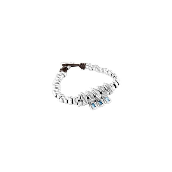Distinguished Japanese-inspired metal bracelet that is silver plated and combine with leather straps. It has the iconic UNOde50 engraving on its closure and consists of multiple feather-shaped beads where three elegant ones are interspersed inrectangular pieces topped with blue crystal SWAROVSKI® ELEMENTS. In addition, it is made up of silver-plated beads, that give balance to the jewel. Dare to wear this 100% handmade inimitable jewel in Spain. Available in various sizes.